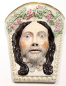 Unusual Staffordshire wall pocket modelled probably as Christ, with a garland of fruit, 24cm long