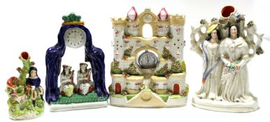 Two Staffordshire watch holder groups, one modelled as a castle, the other flanked by two figures,