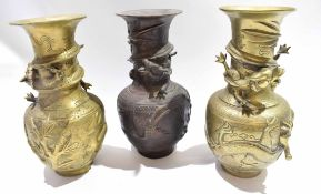 Group of three Oriental metal vases, all decorated in relief with dragons to the neck with further