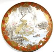Large Satsuma dish, Meiji period, the centre decorated with a landscape scene and mountains with