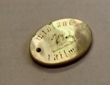 An oval 33 x 25mm mother of pearl Midland Railway free ticket token with hole for suspension.