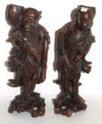 Pair of carved wooden Chinese figures on scroll bases (2)