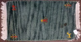 Late 20th century small thick green woollen pile prayer rug with animal motifs to corners and