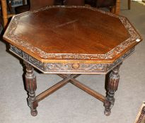 Oak dining table of octagonal form, carved top and frieze decorated with floral C-scrolls raised