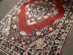 Early/mid-20th century Caucasian wool rug in cream, blue and beige patterns to a red ground with