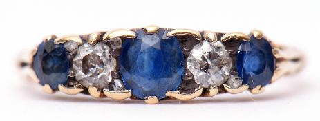 Antique sapphire and diamond ring featuring three circular shaped sapphires and two small