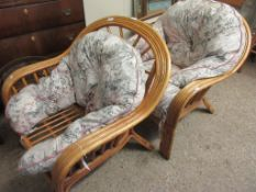 TWO BAMBOO FRAMED ARMCHAIRS WITH FLORAL UPHOLSTERED CUSHIONS