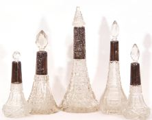 Mixed Lot: five late 19th/early 20th century cut glass tapering scent bottles with hallmarked silver
