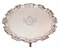 "George V plain small silver waiter of circular form with ""Chippendale"" edge and supported on four"