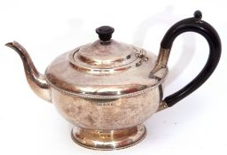 George V silver tea pot of compressed circular form on a spreading foot, beaded rim decoration,