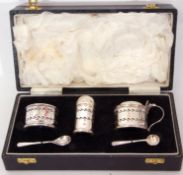 Cased three piece silver cruet set comprising salt with blue glass liner, pepper pot with pull off