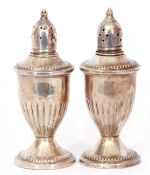 Pair of antique silver loaded peppers of vase form, pierced detachable tops, half fluted bodies,