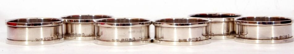 Six George V silver napkin rings of circular form, plain polished design with raised edges,
