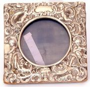 Victorian small silver photograph frame of square form, elaborately decorated with cherubs,