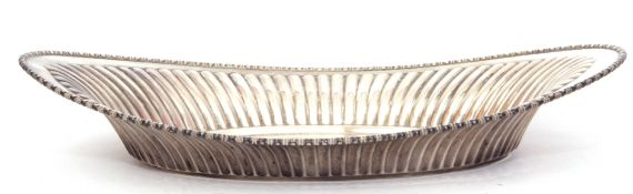 "White metal bread roll dish of shaped oval form, fluted body with beaded rim, stamped ""Sterlnig"","