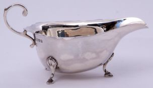 George V sauce boat in early Georgian style, having card cut rim, flying scrolled handle and