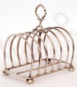 Late Victorian six slice toast rack, the wirework design with central carrying ring handle on a