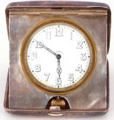 George V silver cased travelling clock the plain polished case with hinged door, the clock with