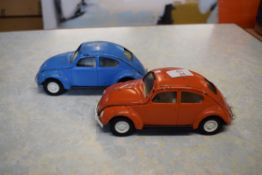 Two Tonka models of Volkswagen Beetles, one in red, the other in blue livery