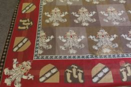 Large 20th century wool work wall hanging in heraldic style, the border featuring various shields,