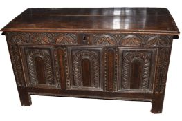 18th century polished and carved oak coffer having three arched carved panels below a lunette