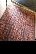Early/mid-20th century Belouch style wool rug with repeating geometric patterns in blue to a red