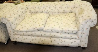 Matched pair of late Victorian Chesterfield sofas both upholstered in matching floral button back (