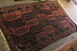 Early/mid 20th century Bokhara type wool rug with repeating geometric patterns in black to a red