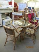 GLASS TOPPED CANE CIRCULAR CONSERVATORY DINING TABLE, TOGETHER WITH FOUR MATCHING CARVER CHAIRS, THE