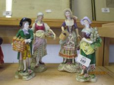FOUR CONTINENTAL PORCELAIN FIGURINES OF STREET SELLERS ON TYPICAL GILT SCROLL BASES