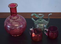 Group of four glass wares including a globular ruby decanter, two small cups and a further green