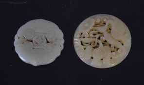 Two green jade medallions, one carved with birds, the other with a geometric design (2)
