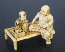 Ivory group of a man and child seated on a table, Meiji period, 6cm long
