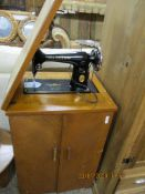 SMALL 1950S SEWING MACHINE CABINET CONTAINING A SINGER SEWING MACHINE SERIAL NO EE533567, CABINET