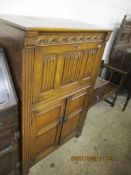 MID-20TH CENTURY CARVED HEAVY OAK REPRODUCTION COCKTAIL CABINET WITH LINENFOLD AND OTHER PANELLED