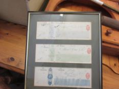 FRAME CONTAINING THREE FRAMED VINTAGE CHEQUES