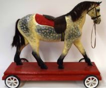 20th century wooden child~s painted horse with later base on wheels