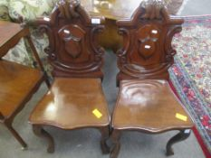Pair of Victorian mahogany hall chairs with C-scroll moulded arch backs solid seats and cabriole