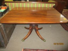 Regency period mahogany pedestal dining table raised on a quadruped base with brass caps and