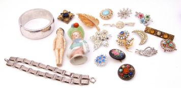 Two trays to include a large modern metal hinged bracelet, a cushion doll, various costume brooches,