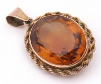 Amber coloured glass faceted oval pendant framed in a rope twist mount stamped 9ct, 28 x 22mm