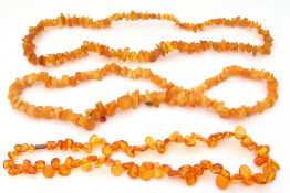 Mixed Lot: polished amber flat bead necklace of irregular form, together with two natural amber