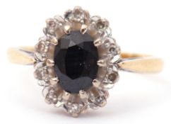 18ct gold sapphire and diamond cluster ring, the oval faceted dark sapphire set within 10 small
