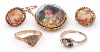 Hand painted porcelain brooch depicting a young man playing a tambourine, in a rope twist mount