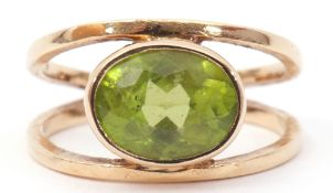 9ct gold peridot ring, the oval faceted peridot bezel set between split plain polished shoulders,