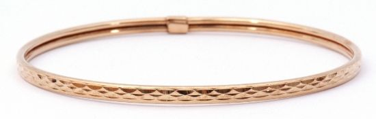 9ct gold bangle with a continuous stylised engraved design, 7cm diam, 3.7gms