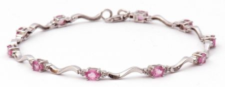 Modern 750 stamped pink sapphire and diamond set articulated bracelet, featuring 10 oval pink