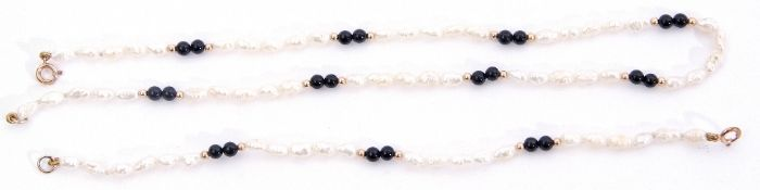 Matching necklace and bracelet of white freshwater cultured pearls interspersed by pairs of black