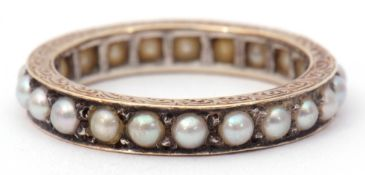 Precious metal and seed pearl eternity ring, the engraved and chased shank with a continuous row