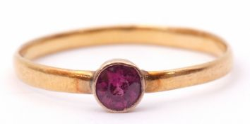 Antique 22ct gold ring with a small circular pink ruby in a collet setting, to a plain polished